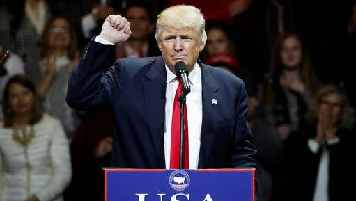 President-elect Donald Trump raises his fist as he speaks during the first stop of his post-election tour, Thursday, Dec. 1, 2016, in Cincinnati.