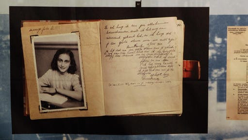 """FILE - This June 12, 2009 file photo, shows a photo of Anne Frank at the opening of the exhibition: """"Anne Frank, a History for Today"""", at the Westerbork Remembrance Centre in Hooghalen, northeast Netherlands. A new study by the Anne Frank House museum in Amsterdam said Friday, Dec. 16, 2016, there is no conclusive evidence that the Jewish diarist and her family were betrayed to the Netherlands' German occupiers during World War II, leading to their arrest and deportation."""