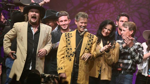 "Travis Tritt, from left, Michael Ray, Randy Travis, Mary Travis and Ricky Traywick appear on stage at the ""1 Night. 1 Place. 1 Time.: A Heroes and Friends Tribute to Randy Travis"" at Bridgestone Arena on Wednesday, Feb. 8, 2017 in Nashville, Tenn."