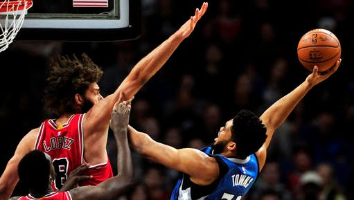 Minnesota Timberwolves center Karl-Anthony Towns (32) shoots against Chicago Bulls' Bobby Portis (5) and Robin Lopez (8) during the first quarter of an NBA basketball game on Sunday, Feb. 12  in Minneapolis.