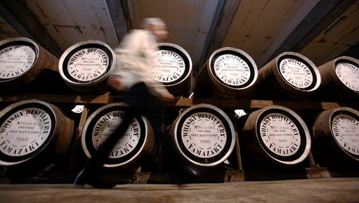 """In this March 8, 2017 photo, Suntory's chief blender Shinji Fukuyo walks by wooden whisky barrels in a warehouse at the Suntory distillery in Yamazaki, near Kyoto, western Japan. """"What's important for whisky is that its deliciousness must deepen with aging, sitting in the casks for a long time,"""" said Fukuyo, 55, demonstrating how he examines the whisky in a glass, swirling the crystalline amber spirit against the light."""