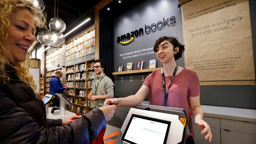 FILE - In this Tuesday, Nov. 3, 2015, file photo, customer Kirsty Carey, left, gets ready to swipe her credit card for clerk Marissa Pacchiarotti, as she makes one of the first purchases at the opening day for Amazon Books, the first brick-and-mortar retail store for online retail giant Amazon, in Seattle. Although Amazon already dominates e-commerce, 90 percent of worldwide retail spending is still in brick-and-mortar stores, according to eMarketer. Amazon has the chance to change retail with automation and data-mining technologies borrowed from e-commerce.