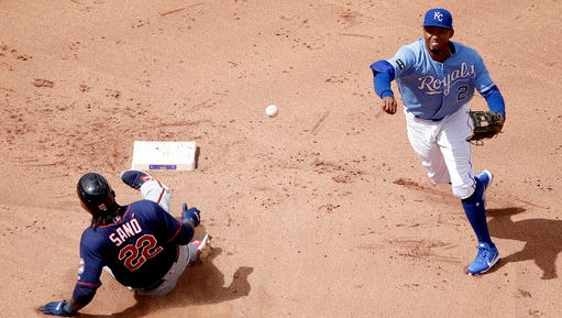 Kansas City Royals shortstop Alcides Escobar, right, throws to first for a double play hit into by Minnesota Twins' Joe Mauer (not shown) after forcing Miguel Sano (22) out at second during the fourth inning of a baseball game Sunday, April 30, in Kansas City, Mo.
