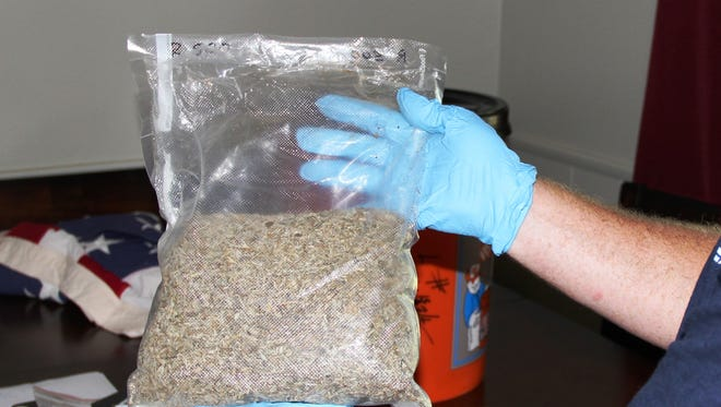 A Drug Task Force agent holds up a bag of synthetic marijuana found at the home of Robert Nolen.