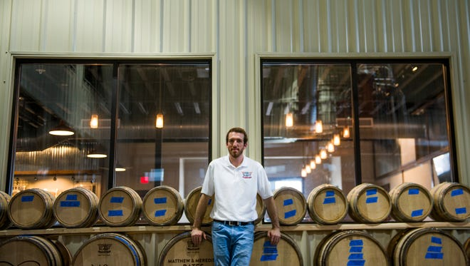 Matt Cunningham poses for a portrait next to aging whiskey barrels inside his distillery on July 19, 2017.
