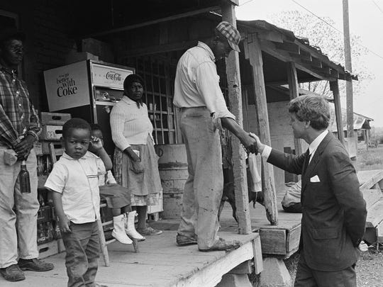 Sen. Robert F. Kennedy (D-N.Y.), offers a handshake to a resident of the rural Mississippi Delta near Greenville, Miss., April 12, 1967, during a tour of the area in connection with a Senate subcommittee investigation into the anti-poverty program.  (AP Photo/Jack Thornell)