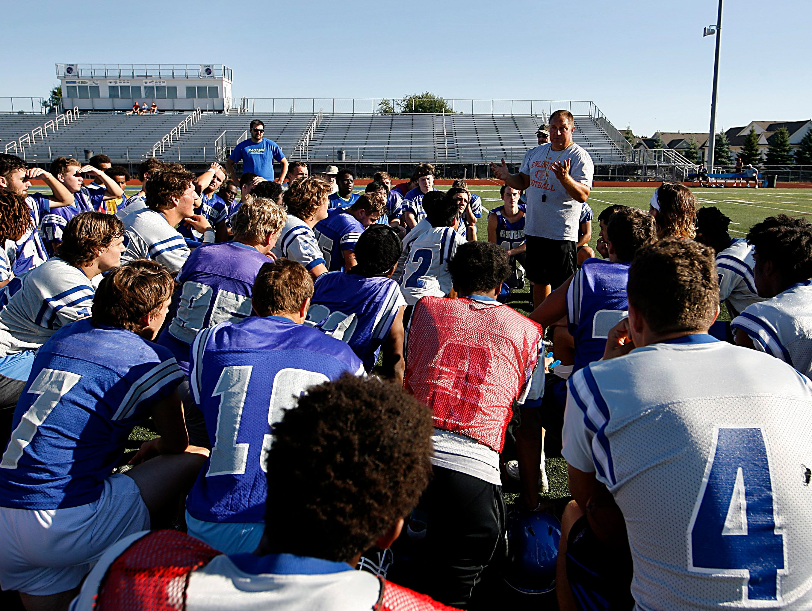 Walled Lake Western coach Mike Zdebski talks to his team a break during their first practice of the season Monday.