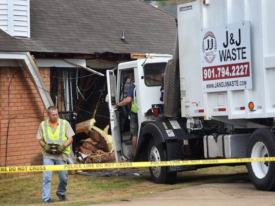 October 5, 2016 - Employees with Visual Towing work to remove a garbage truck that crashed into a house on Cedargreen Cove in Northeast Shelby County. The driver was taken to a local hospital.