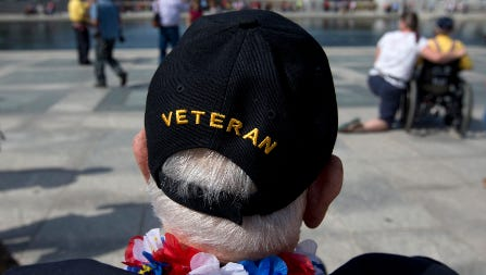 George Bloss, from Gulfport, Miss., and other veterans cross barricades to visit the national World War II Memorial in Washington on the first day of the government shutdown.