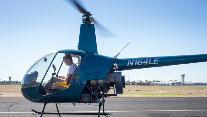 An aviation expert performs maintenance on a Robinson R22 helicopter.