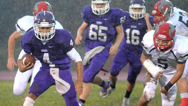 Indians' quarterback Deondre Cook looks for room to run against Elgin last weekend at Mount Gilead High School.