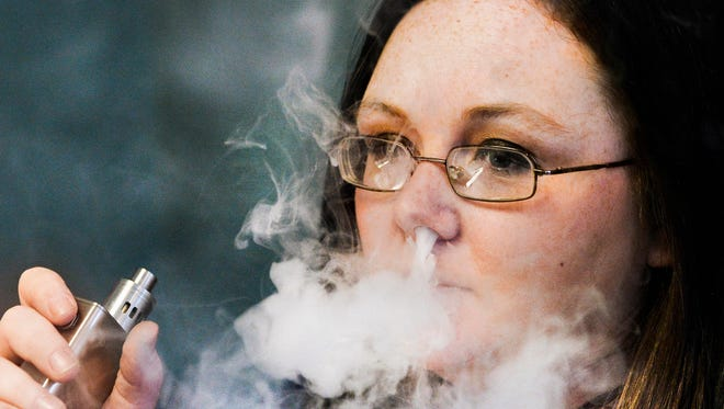 In this 2016 photo, Stephanie Wilson, an employee at Breathe Vapor, a retail shop that specializes in electronic cigarettes, exhales vapor at the store in East Peoria, Ill.