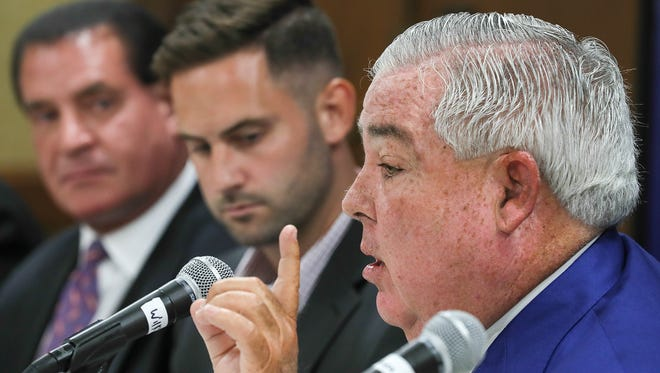 Lawyer John Morgan makes a point alongside former Louisville basketball player Luke Hancock at Wednesday's press conference announcing a lawsuit against the NCAA. July 11, 2018