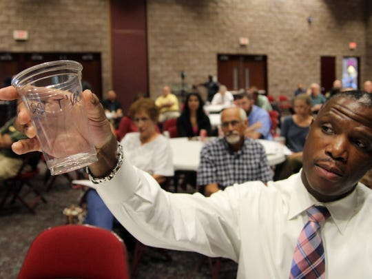 A man holds up a cup with mosquito larvae at a Zika forum in Anderson County.