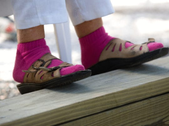 Woman's feet atop wooden railing