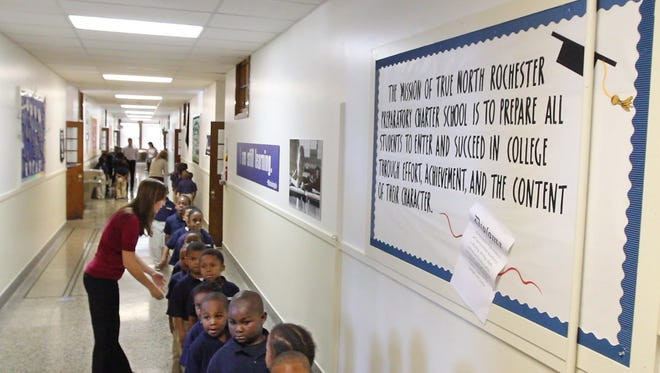 Kindergarten teacher Kimberly Kreskow helps her students keep their line straight as they head down the hallway during a transition period at True North Rochester Prep Elementary School on Jay Street. At right is a bulletin board that spells out the schoolâ?'s goals.