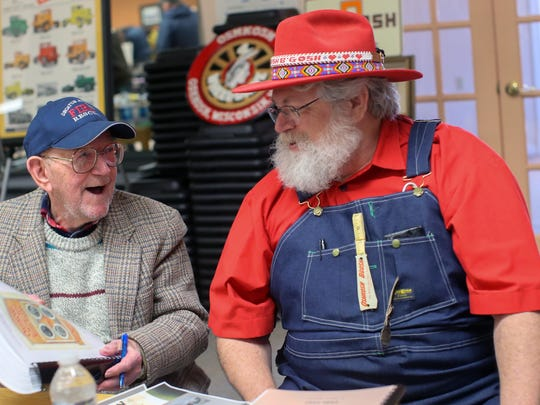 "Ninety-five-year-old Clarence ""Inky"" Jungwirth, left, autographs his book for Tom Beyer wearing Oshkosh B'Gosh clothing while at the Oshkosh Memorabilia Club show March 21, 2015, at the Oshkosh Senior Center."