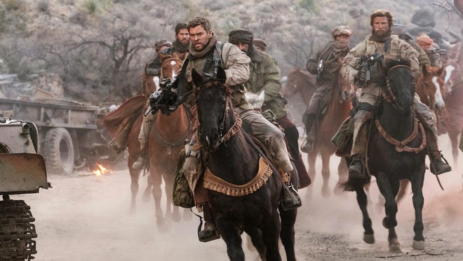 """This image released by Warner Bros. Entertainment shows Chris Hemsworth, center, in a scene from """"12 Strong."""""""