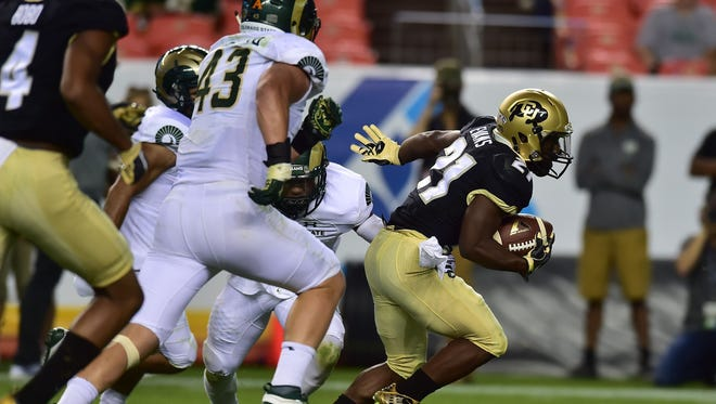 Colorado running back Kyle Evans gets away from CSU defenders while running for a 1-yard touchdown Friday in the Buffs' 44-7 win over the Rams in Denver. CU gained 578 yards of total offense against an inexperienced CSU defense.