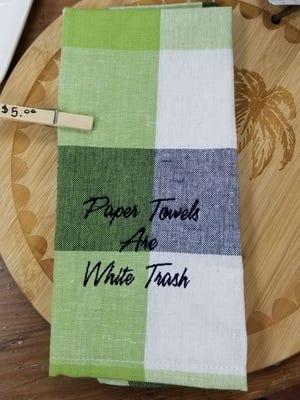 """JAR's kitchen towels with the words """"Paper Towels are White Trash"""" sold out twice during the grand opening. Brandi Kneip had a  a local printer, Reel Graphics make more on the spot only to sell them out again."""