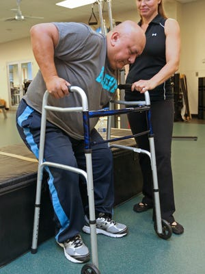 Pedro Toala his personal trainer Kristi Smith-Willis watches as he uses a walker to get back to motorized wheelchair, at the Hockessin Athletic Club.
