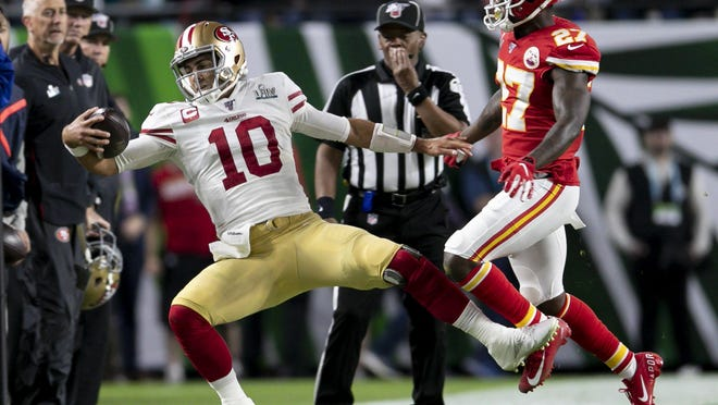San Francisco's #10 Jimmy Garoppolo runs out of bounds in front of Kansas City's #27 Rashad Fenton during the fourth quarter of Super Bowl LIV at Hard Rock Stadium in Miami Gardens, Feb. 2, 2020.