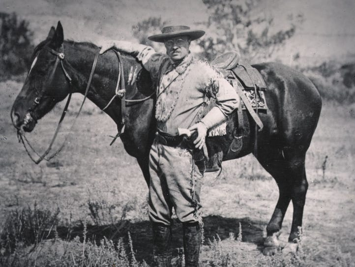 President Theodore Roosevelt stands with a saddled