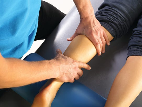 The doctor orthopedist, physical therapist examines