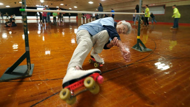 Eighty two-year-old Joanie Clark glides effortlessly on one roller skate under a limbo bar at Skateland on Sunday, Feb. 21, 2016.