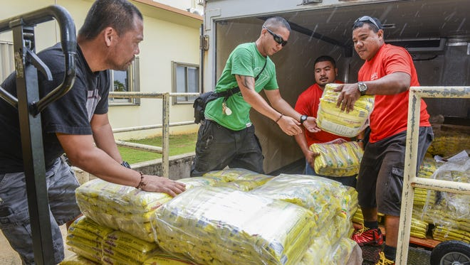 In this Nov. 23, 2016, file photo, staff of The Salvation Army and Quality Distributors employees unload some of the 2,160 two-pound bags of rice the company donated.