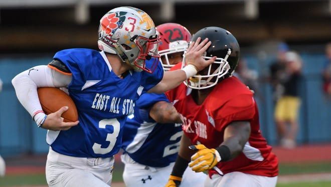 East quarterback Seth Becker, of Bethel-Tate, evades a defender in the Ron Woyan Southwest Ohio Football Coaches Association East/West All-Star Game on Thursday, June 7, 2018, at Kings High School.