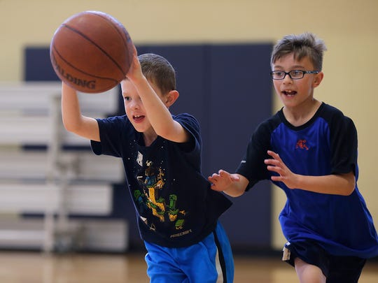 At left, Ashton Seeley, 7, and Luke Wainio, 9, play a game of basketball during the after-school program at the Salvation Army's Ray & Joan Kroc Corps Community Center in Green Bay on Monday, June 6, 2016.