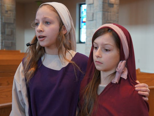 """Abby Bowe, left, and Sophia Loehr practice the opening scene of Shepherd of the Hills Catholic School's dramatization of """"The Living Way of the Cross."""""""