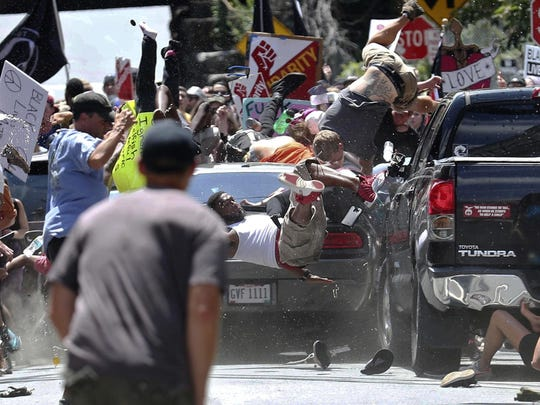 People fly into the air as a vehicle is driven into a group of protesters demonstrating against a white nationalist rally in Charlottesville, Va. on Aug. 12, 2017. James Alex Fields Jr., the man accused of driving into the crowd demonstrating against a white nationalist protest, killing one person and injuring many more, heads to court Monday.
