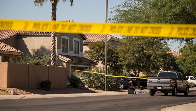 Crime scene tape surrounds a Gilbert neighborhood on Sunday, Oct. 11, 2015, following a double homicide.