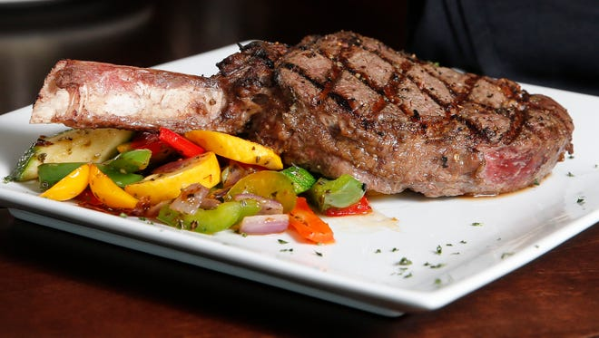 The bone-in ribeye steak, served with sautŽeed vegetable medley