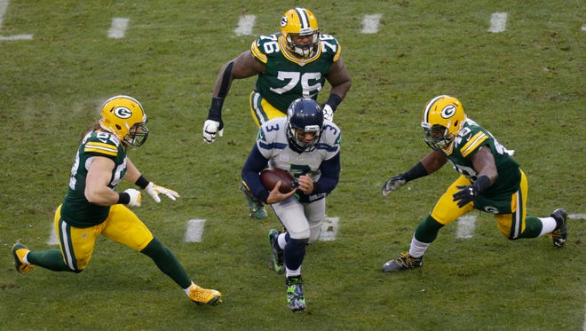Green Bay Packers linebacker Clay Matthews (52), defensive end Mike Daniels (76) and linebacker Joe Thomas (48) pursue Seattle Seahawks quarterback Russell Wilson (3) during the first quarter on Dec. 11, 2016, at Lambeau Field.