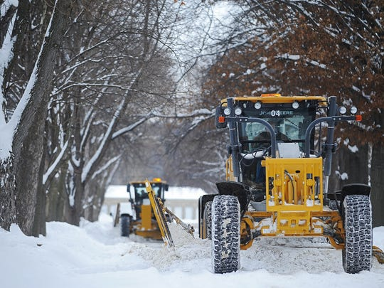 Snow is removed from South 5th Avenue between 38th and 41st Streets Tuesday, Dec. 29, 2015, in Sioux Falls.