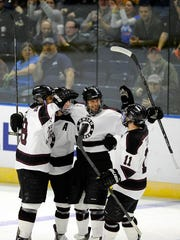 Union players celebrate their first goal against Vermont during the first period of a game in the men's NCAA East Regional hockey tournament Friday, March 28, 2014, in Bridgeport, Conn.