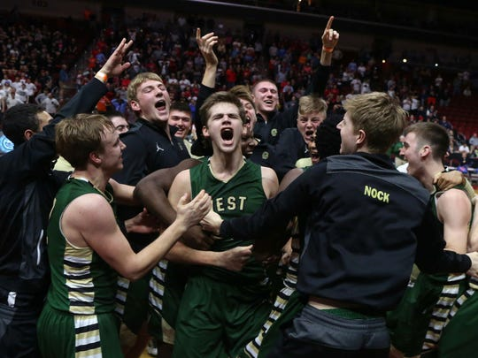 Members of the Iowa City West basketball team surround senior Tanner Lohaus after Lohaus tipped in the game-winning shot in the final second against Cedar Falls on Friday, March 11, 2016, at Wells Fargo Arena in Des Moines.