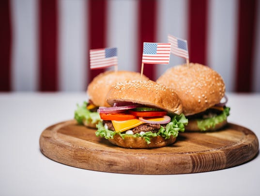 Three cheeseburgers with little american flags on wooden board