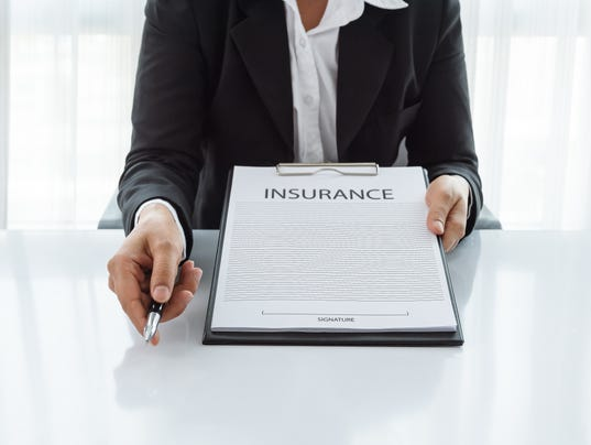 woman in suit in his office showing and insurance policy