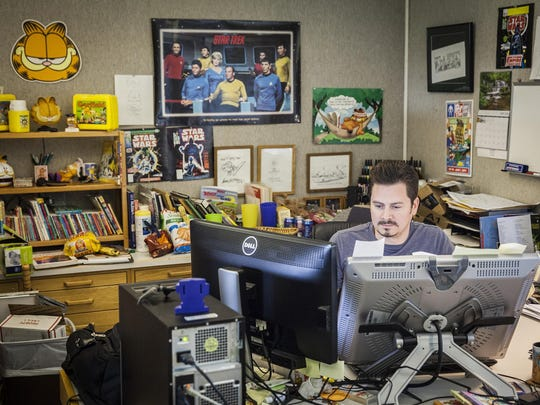 Paws, Inc. social media and creative director David Reddick works at his desk in Albany.