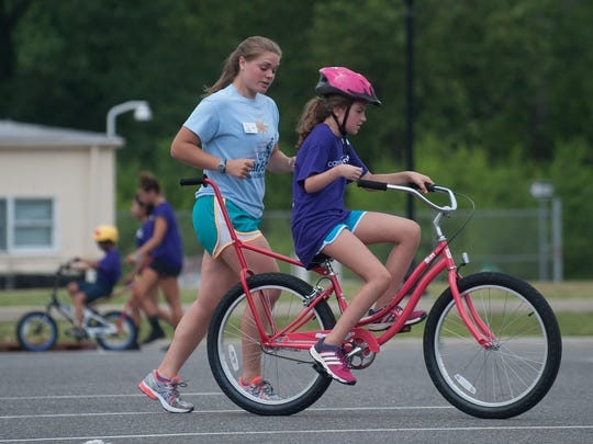 Layla Williams rides her bike with the help of Kelly Robichaud during  the bike camp.