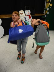 Annamarie and Tiffany Williams head out with their backpacks of gifts after meeting Santa.
