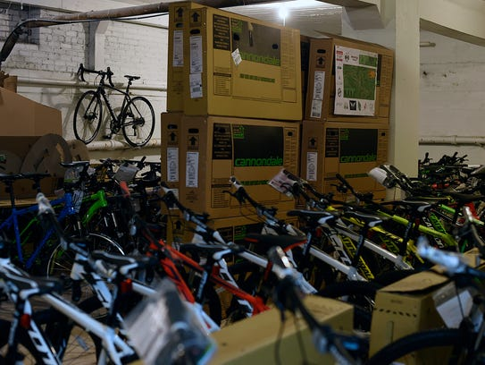 Dozens of newly built bicycles sit in a room as Immel