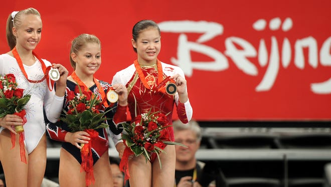 U.S. gymnast Shawn Johnson (center) shows off her gold medal with USA silver medalist Nastia Liukin (left) and China's Fei Cheng after the balance beam Gymnastic Artistic Finals on Aug. 19, 2008.