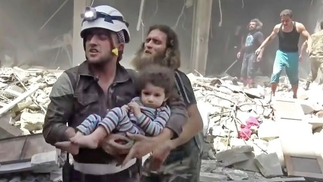 In this image made from video and posted online by Validated UGC on Thursday, April 28, 2016, a civil defense worker carries a child after airstrikes hit Aleppo, Syria.
