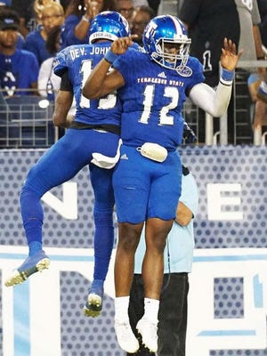 Tennessee State receiver DeVon Johnson, left, and quarterback Michael Hughes (12) celebrate after hooking up for a touchdown pass in the Tigers last game against Austin Peay.