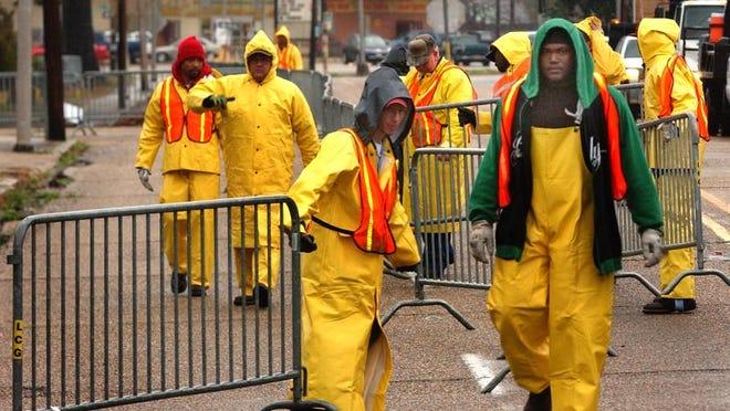 Lafayette Public Service workers set up barricades for the Mardi Gras parades along Jefferson Street.